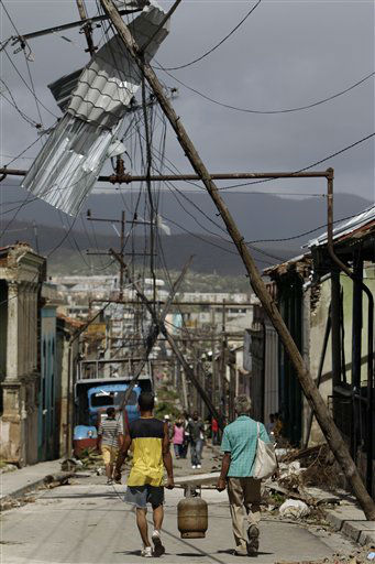 "<div class=""meta ""><span class=""caption-text "">Men carry a gas container through a street that was damaged by Hurricane Sandy in Santiago de Cuba, Cuba, Friday Oct. 26, 2012. (AP Photo/ Franklin Reyes)</span></div>"