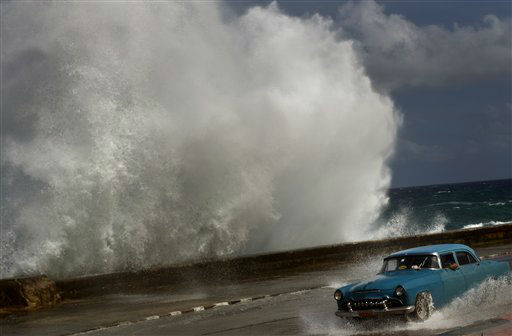 A driver maneuvers his classic American car along a wet road as a wave crashes against the Malecon in Havana, Cuba, Thursday, Oct. 25, 2012.   <span class=meta>(AP Photo&#47; Ramon Espinosa)</span>