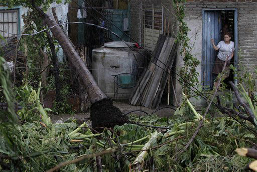 "<div class=""meta ""><span class=""caption-text "">A woman stands at the entrance of her house in front of a fallen palm tree after the passing of Hurricane Sandy in Santiago de Cuba, Cuba, Thursday Oct. 25, 2012.   (AP Photo/ Franklin Reyes)</span></div>"