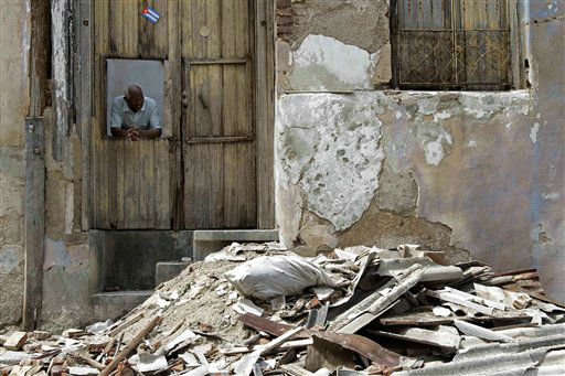 A man peers from the window of his home where debris lays in the street after the passing of Hurricane Sandy in Santiago de Cuba, Cuba, Friday Oct. 26, 2012.  <span class=meta>(AP Photo&#47; Franklin Reyes)</span>