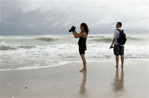 Tourists Stephanie and Dan Koch of Atlantic City, N.J. take a photograph of high surf as Hurricane Sandy passes offshore to the east, Friday, Oct. 26, 2012, in Miami Beach, Fla. <span class=meta>(AP Photo&#47; Lynne Sladky)</span>