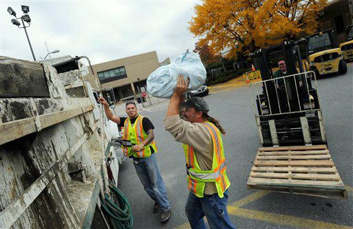 Baltimore Gas &amp; Electric &#40;BGE&#41; workers Jordan Sauer, left, and William MacAleese, load plastic bags to be filled with sand at a BGE storage yard in Baltimore Friday, Oct. 26, 2012.  <span class=meta>(AP Photo&#47; Steve Ruark)</span>