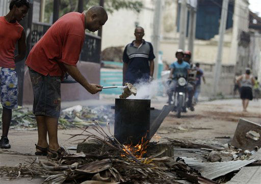 "<div class=""meta ""><span class=""caption-text "">A man uses burning wood to cook a traditional ""caldosa,"" a pot of food cooked and shared among neighbors, while gas and electricity are down after the passing of Hurricane Sandy in Santiago de Cuba, Cuba, Friday Oct. 26, 2012.  (AP Photo/ Franklin Reyes)</span></div>"
