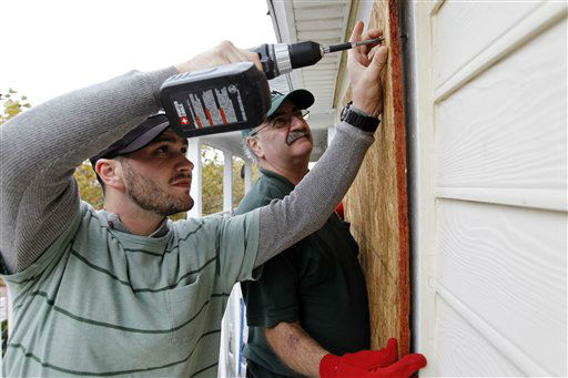 "<div class=""meta ""><span class=""caption-text "">Scott Viviano, foreground, helps his friends to board up the windows of their home as Hurricane Sandy approaches the Atlantic Coast in Ocean City, Md., on Saturday, Oct. 27, 2012.  (AP Photo/ Jose Luis Magana)</span></div>"