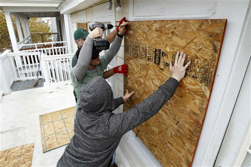 "<div class=""meta ""><span class=""caption-text "">Scott Viviano, holding the drill, helps his friends to board up the windows of their home as Hurricane Sandy approaches the Atlantic Coast, in Ocean City, Md., on Saturday, Oct. 27, 2012.  (AP Photo/ Jose Luis Magana)</span></div>"