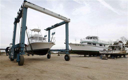 A 50-ton lift raises fishing boat MegaBites II out of the Maurice River and past others put on land at Yank Marine Services marina Saturday, Oct. 27, 2012, in Dorchester, N.J., in preparation for Hurricane Sandy.  <span class=meta>(AP Photo&#47; Mel Evans)</span>