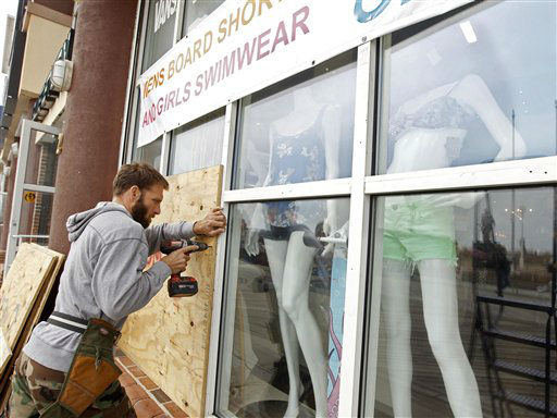 "<div class=""meta ""><span class=""caption-text "">A worker boards up the windows of the store as Hurricane Sandy approaches in Ocean City, Md., on Saturday,  Oct. 27,  2012.  (AP Photo/ Jose Luis Magana)</span></div>"