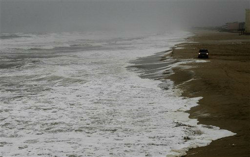 A vehicle drives along the beach as waves generated by Hurricane Sandy crash ashore in Nags Head, N.C., Saturday, Oct. 27, 2012.  <span class=meta>(AP Photo&#47; Gerry Broome)</span>