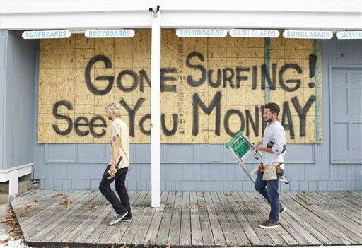 Store workers Fletcher Birch, right, and Jay Kleman finish boarding up the windows on a surf store in Ocean City, Md. on Saturday, Oct. 27, 2012 as Hurricane Sandy approaches the Atlantic coast.  <span class=meta>(AP Photo&#47; Jose Luis Magana)</span>