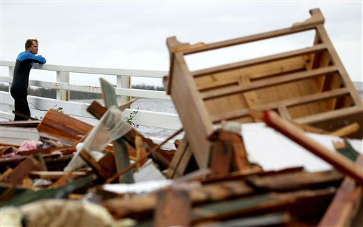 "<div class=""meta ""><span class=""caption-text "">Currie Wagner looks at the wreckage of his grandmother Betty Wagner's house, which was destroyed and wound up resting on top of the Mantoloking Bridge the morning after hybrid storm Sandy rolled through, Tuesday, Oct. 30, 2012, in Mantoloking.  (AP Photo/ Julio Cortez)</span></div>"
