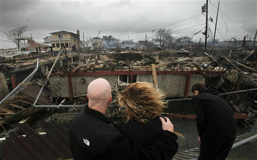 Robert Connolly, left, embraces his wife Laura as they survey the remains of the home owned by her parents that burned to the ground in the Breezy Point section of New York, Tuesday, Oct. 30, 2012.  <span class=meta>(AP Photo&#47; Mark Lennihan)</span>