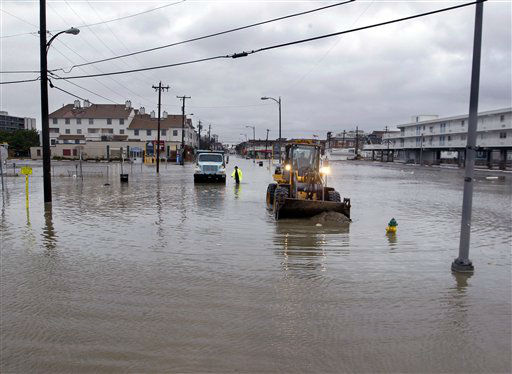 Crews work in flooded streets Tuesday, Oct. 30, 2012, in Ocean City, N.J., as they try to open drains and push the sand back toward the beach after the storm surge from Sandy flooded much of the town.  <span class=meta>(AP Photo&#47; Mel Evans)</span>