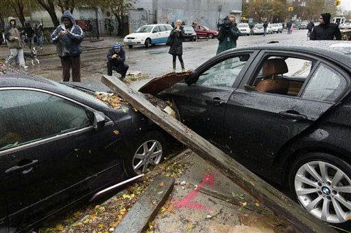 Onlookers take photographs of two cars that collided during flooding outside the Consolidated Edison power sub-station on 14th Street, Tuesday, Oct. 30, 2012, in New York. <span class=meta>(AP Photo&#47; John Minchillo)</span>