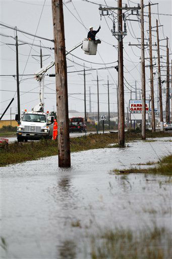 "<div class=""meta ""><span class=""caption-text "">A crew works on power poles Tuesday, Oct. 30, 2012, near Ocean City, N.J., after a storm surge from Sandy pushed the Atlantic Ocean over the beach and across streets.  (AP Photo/ Mel Evans)</span></div>"
