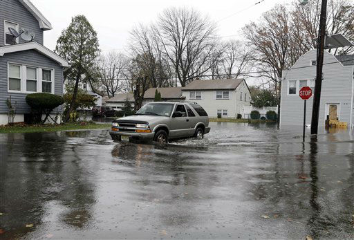 A vehicle is driven along a flooded street in the wake of superstorm Sandy on Tuesday, Oct. 30, 2012, in Little Ferry, N.J.  <span class=meta>(AP Photo&#47; Mike Groll)</span>