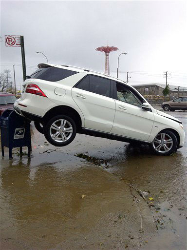 A car is upended on a mailbox on Surf Avenue in Coney Island, N.Y., in the aftermath of Sandy on Tuesday, Oct. 30, 2012.
