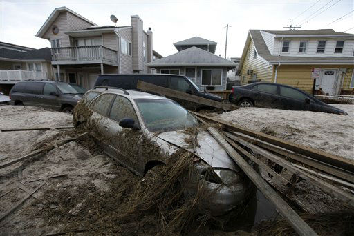A car lies buried in sand and debris in the...