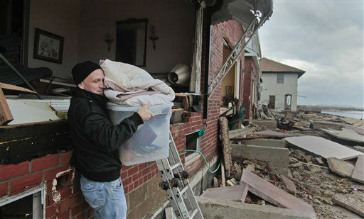 "<div class=""meta ""><span class=""caption-text "">Peter Andrews removes belongings from his father's beachfront home, destroyed in the aftermath of a storm surge from superstorm Sandy, Tuesday, Oct. 30, 2012, in Coney Island's Sea Gate community in New York.   (AP Photo/ Bebeto Matthews)</span></div>"