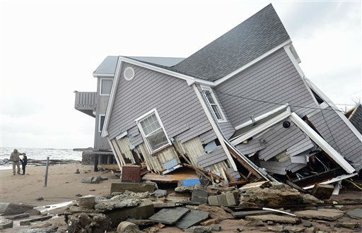 People stand next to a house collapsed from...