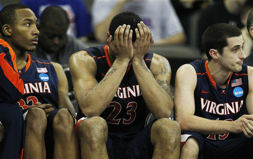 Virginia forward Mike Scott &#40;23&#41; holds his  head while on the bench with teammates Darion Atkins &#40;32&#41; and Sammy Zeglinski &#40;13&#41; during the second half of an NCAA college basketball tournament game against Florida at CenturyLink Center in Omaha, Neb., Friday, March 16, 2012. Florida defeated Virginia 71-45.  <span class=meta>(AP Photo&#47; Orlin Wagner)</span>