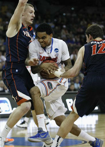 Florida&#39;s Mike Rosario is sandwiched between Virginia&#39;s Paul Jesperson, left, and Joe Harris, in the first half of an NCAA tournament second-round college basketball game at CenturyLink Center in Omaha, Neb., Friday, March 16, 2012.  <span class=meta>(AP Photo&#47; Orlin Wagner)</span>