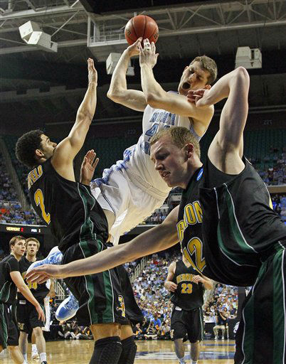 "<div class=""meta ""><span class=""caption-text "">North Carolina's Tyler Zeller (44) falls as he drives between Vermont's Luke Apfeld (2) and Sandro Carissimo (12)  during the first half of a Midwest Regional NCAA tournament second-round college basketball game in Greensboro, N.C., Friday, March 16, 2012. (AP Photo/ Gerry Broome)</span></div>"