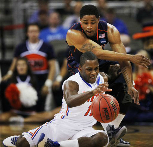 Florida guard Erving Walker &#40;11&#41; controls the ball while covered by Virginia guard Jontel Evans &#40;1&#41; during the first half of a second-round NCAA college basketball tournament game at CenturyLink Center in Omaha, Neb., Friday, March 16, 2012.  <span class=meta>(AP Photo&#47; Nati Harnik)</span>