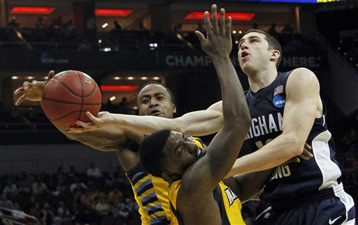 BYU guard Matt Carlino, right, drives the lane as Marquette guard Darius Johnson-Odom, front, and Marquette guard Junior Cadougan, left, defend in the second half of their NCAA tournament second-round college basketball game in Louisville, Ky., Thursday, March 15, 2012. <span class=meta>(AP Photo&#47; Dave Martin)</span>