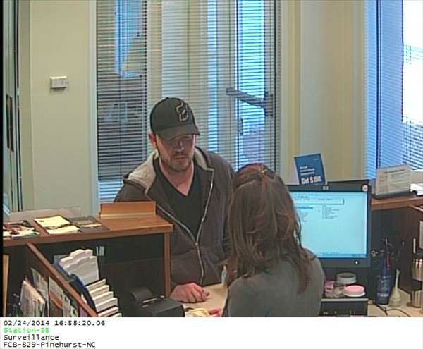 "<div class=""meta ""><span class=""caption-text "">Police in Pinehurst are looking for the suspect who robbed the First Citizens Bank on Page Drive and Avimore Drive at 5 p.m. Monday. He is described as a 30-year-old white male, wearing a black shirt, black jacket with a fur collar, and a black baseball cap. The suspect was last seen leaving in a tan/gold colored Chevy Colbalt. (WTVD Photo/ Pinehurst Police)</span></div>"