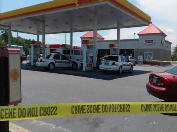 Officers investigate at a gas...