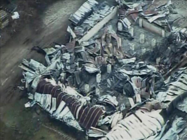 Pictures from Chopper 11 HD showed the Southern States Farm Supply building in Warrenton continued to smolder Thursday morning. <span class=meta>(WTVD Photo&#47; Chopper 11 HD)</span>