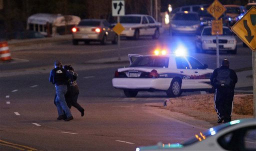 Police run with a hostage at a Wachovia Bank in Cary, N.C., where an armed man took people hostage Thursday, Feb. 10, 2011.  <span class=meta>(AP Photo&#47; Gerry Broome)</span>