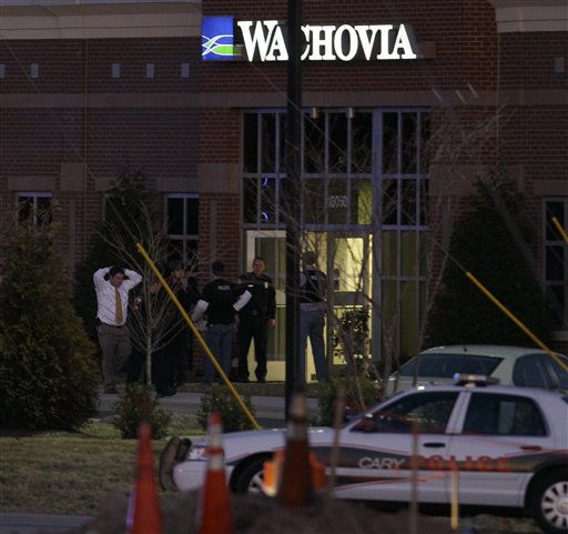 A hostage is led from a Wachovia Bank in Cary, N.C., where an armed man took people hostage Thursday, Feb. 10, 2011.  <span class=meta>(AP Photo&#47; Gerry Broome)</span>