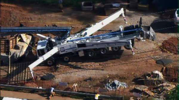 "<div class=""meta image-caption""><div class=""origin-logo origin-image ""><span></span></div><span class=""caption-text"">Concrete pumping truck with long boom arm topples over at work site off Tryon Road in Cary Wednesday morning. (Photo/Chopper11 HD)</span></div>"