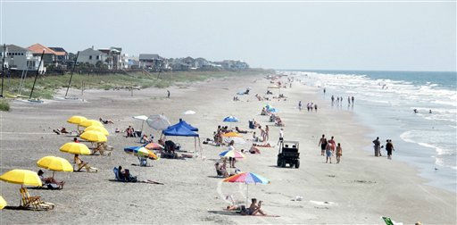 Beachgoers sit and walk in the sun at Folly Beach, S.C., on Tuesday, Aug. 23, 2011, as Hurricane Irene spins hundreds of miles at sea. <span class=meta>(AP Photo&#47; Bruce Smith)</span>