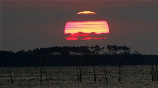 "<div class=""meta image-caption""><div class=""origin-logo origin-image ""><span></span></div><span class=""caption-text"">A setting sun is seen across the Croatan Sound near Manteo, N.C., Tuesday, Aug. 23, 2011. Hurricane Irene threatens the North Carolina Outer Banks as it moves up the east coast.  (AP Photo/ Gerry Broome)</span></div>"
