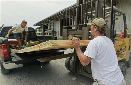 Tim Waterfield, left, and Byron Wilson, an employee with Dare Building supply, load plywood into Waterfield&#39;s truck in Buxton, N.C., Wednesday, Aug. 24, 2011.  <span class=meta>(AP Photo&#47; Gerry Broome)</span>