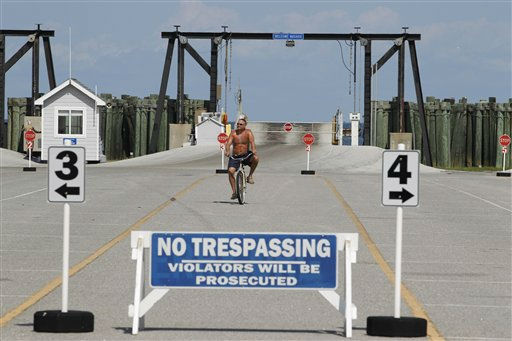 Tourist Neil Marcella of Yorktown Va. rides his bike in an empty ferry parking at Cape Hatteras, N.C. as evacuations from Ocracoke Island began Wednesday, Aug. 24, 2011 in preparation for Hurricane Irene.  <span class=meta>(AP Photo&#47; Jose Luis Magana)</span>