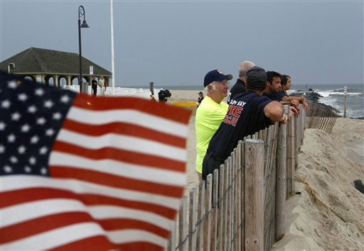 "<div class=""meta ""><span class=""caption-text "">As a small American flag flaps in the wind, members of the Cape May Fire Department and others look out from the southern end of the boardwalk at a stormy Atlantic early Saturday, Aug. 27, 2011, in Cape May, N.J. , as Hurricane Irene approaches.  (AP Photo/ Mel Evans)</span></div>"