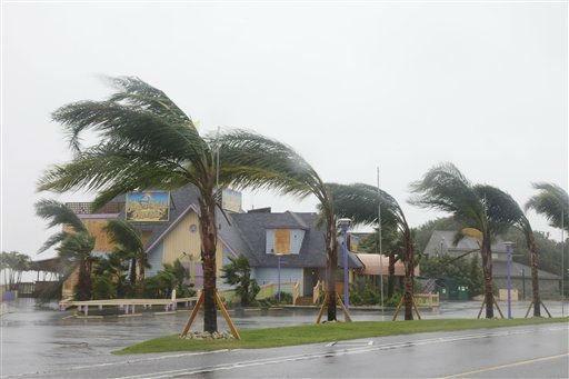 A boarded up restaurant is seen behind palm trees as they bend in the strong winds on the Outer Banks in Duck, N.C., Saturday, Aug. 27, 2011 <span class=meta>(AP Photo&#47; Charles Dharapak)</span>