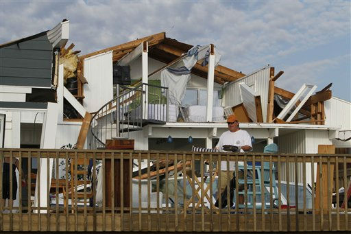 "<div class=""meta ""><span class=""caption-text "">Casey Robinson clears out belongings from his severely storm-damaged beach home in the Sandbridge area of Virginia Beach, Va., after Hurricane Irene hit the region, Sunday, Aug. 28, 2011. (AP Photo/ Steve Helber)</span></div>"