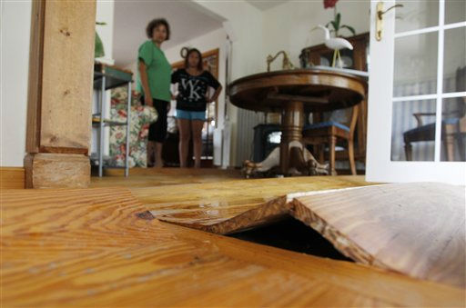 The wooden floor is warped and buckled from flooding as Lechelle and Haleigh Spalding stand in the living room of their flooded home on the Outer Banks in Kitty Hawk, N.C., Sunday, Aug. 28, 2011 <span class=meta>(AP Photo&#47; Charles Dharapak)</span>