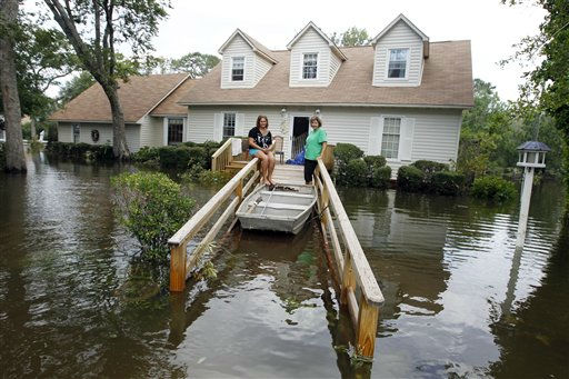 Lechelle, right, and her daughter Haleigh Spalding sit in front of their flooded home after a storm surge on the Outer Banks in Kitty Hawk, N.C., Sunday, Aug. 28, 2011  <span class=meta>(AP Photo&#47; Charles Dharapak)</span>