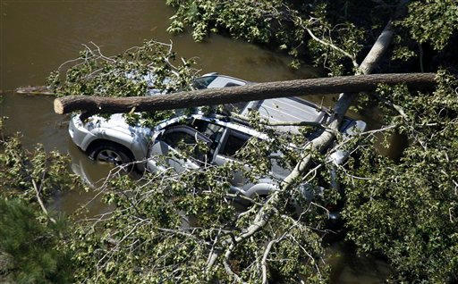 "<div class=""meta ""><span class=""caption-text "">A vehicle is covered by trees on a flooded roadway in Southern Shores, N.C., Sunday, Aug. 28, 2011. (AP Photo/ Steve Helber)</span></div>"