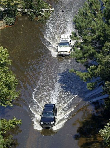 "<div class=""meta ""><span class=""caption-text "">Vehicles make their way through flooded roadways in Souther Shores, N.C., Sunday, Aug. 28, 2011. (AP Photo/ Steve Helber)</span></div>"