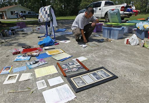"<div class=""meta ""><span class=""caption-text "">Brad Potter looks over family keepsakes he removed from his flooded home in South Creek, N.C., Sunday, Aug. 28, 2011. (AP Photo/ Chuck Burton)</span></div>"