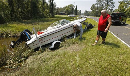 Russell Zurface, right, looks over his niece&#39;s boat and trailer that was carried by floodwaters into a ditch off the highway in South Creek, N.C., Sunday, Aug. 28, 2011. <span class=meta>(AP Photo&#47; Chuck Burton)</span>