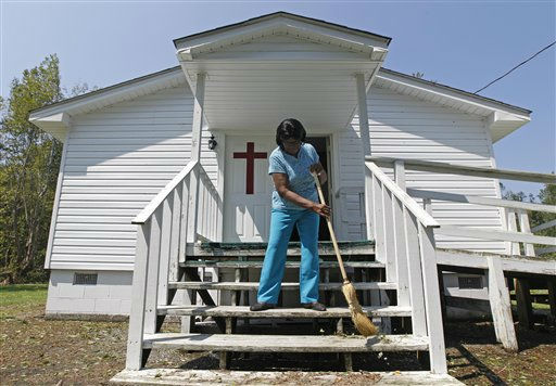 Flora Hill sweeps storms debris from the  Deliverance Temple Holiness Church in Aurora, N.C., Sunday, Aug. 28, 2011. <span class=meta>(AP Photo&#47; Chuck Burton)</span>