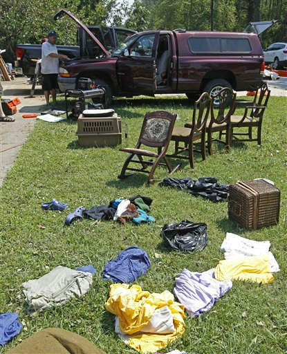 "<div class=""meta ""><span class=""caption-text "">Michael Lannon works on his truck as belongings dry in his front yard in South Creek, N.C., Sunday, Aug. 28, 2011. (AP Photo/ Chuck Burton)</span></div>"