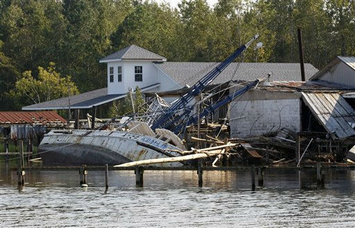 "<div class=""meta ""><span class=""caption-text "">A shrimp boat is bashed against the dock of Daniel's Seafood at the shoreline of the Pamilco River near Aurora, N.C., Sunday, Aug. 28, 2011 after Hurricane Irene hit the North Carolina coast.  (AP Photo/ Chuck Burton)</span></div>"